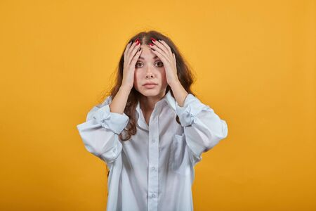 Scared caucasian young woman in fashion white shirt keeping hands on head, looking at camera, confused isolated on orange background in studio. People sincere emotions, lifestyle concept. Imagens