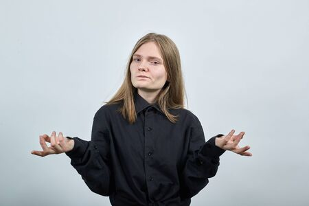 Unhappy caucasian young woman in fashion black shirt isolated on gray background in studio spreads hands, looking aside. People sincere emotions, lifestyle concept.