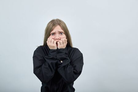 Scared caucasian young woman in fashion black shirt isolated on gray background in studio biting nails, looking surprised. People sincere emotions, lifestyle concept.