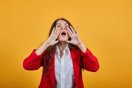 Charming caucasian woman in fashion white shirt and red jacket keeping hands near mouth, screaming, announcing isolated on orange background in studio. People sincere emotions, lifestyle concept.