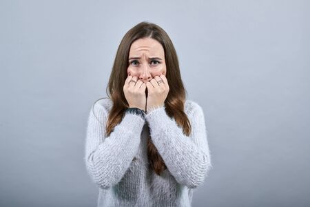Scared attractive caucasian woman wearing nice clothes isolated on gray background in studio biting nails, keeping fists near mouth. People emotions, lifestyle concept.