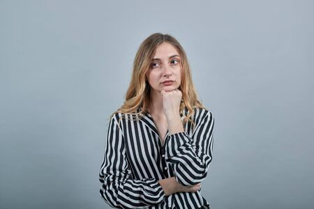 Boring woman in black and white striped shirt looking at camera, keeping fist over chin, keeping hand on stomach isolated on gray background in studio. People sincere emotions, lifestyle concept. Imagens