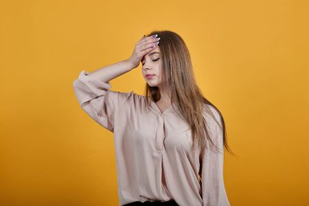 Tired caucasian woman in fashion pastel shirt keeping hand on forehead, having headache isolated on orange background in studio. People sincere emotions, lifestyle concept.