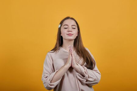 Calm caucasian brunette woman in fashion pastel shirt keeping palms together, praying isolated on orange background in studio. People sincere emotions, lifestyle concept.