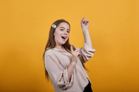 Cheerful caucasian brunette woman in fashion pastel shirt, dancing, keeping fist aside, enjoying isolated on orange background in studio. People sincere emotions, lifestyle concept. Foto de archivo