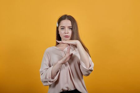 Serious young woman in pastel shirt doing time-out, pause gesture isolated on orange background in studio. People sincere emotions, lifestyle concept. Stok Fotoğraf - 137594097