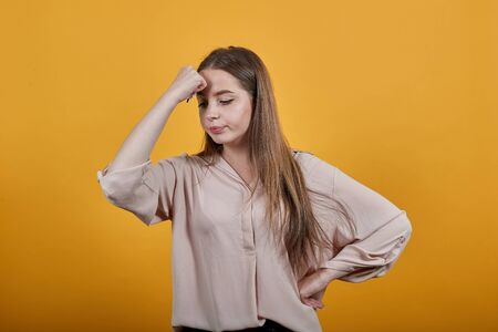Strong caucasian brunette woman in fashion pastel shirt keeping fins on forehead, headache, holding hand on belt isolated on orange background in studio. People sincere emotions, lifestyle concept. Stok Fotoğraf