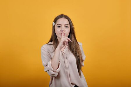Calm caucasian woman in fashion pastel shirt keeping finger on mouth, silence, doing shh gesture isolated on orange background in studio. People sincere emotions, lifestyle concept.
