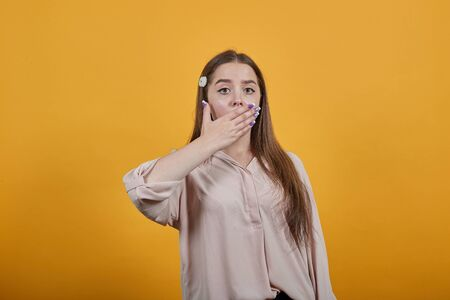 Surprised caucasian brunette woman in pastel shirt covered mouth with palm, opened eyes isolated on orange background in studio. People sincere emotions, lifestyle concept. Stok Fotoğraf - 137596078