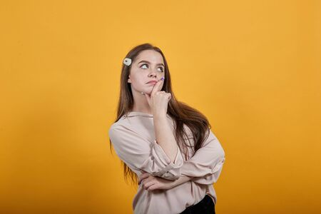 Attractive caucasian young woman staying sideways, hugging her stomach, thinking wearing fashion pastel shirt isolated on orange background in studio. People sincere emotions, lifestyle concept.