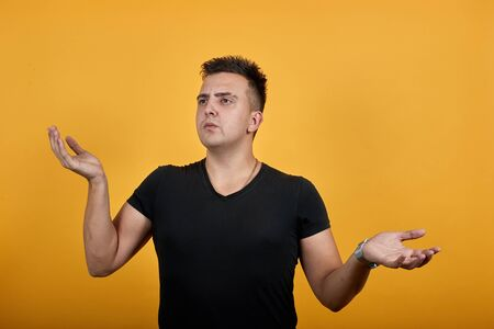 Disappointed young man wearing black shirt isolated on orange background in studio spreads hands, looking into distance. People sincere emotions, lifestyle concept.