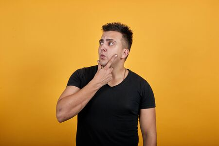 Handsome caucasian young man wearing black shirt isolated on orange background in studio focused, keeping hand on chin, thinking about issue. People sincere emotions, lifestyle concept.