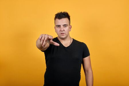 Charming young man wearing black shirt isolated on orange background in studio pointing finger at camera. People sincere emotions, lifestyle concept.