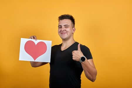 Cheerful young man wearing black shirt isolated on orange background in studio keeping picture with red heart, showing thumb up, smiling. People sincere emotions, lifestyle concept.