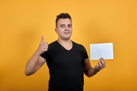 Handsome caucasian young man wearing black shirt isolated on orange background in studio keeping white blank, showing thumb at camera. People sincere emotions, lifestyle concept.