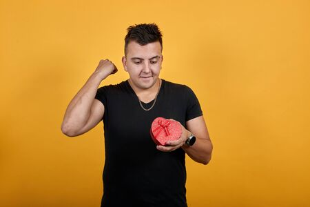 Handsome caucasian young man wearing black shirt isolated on orange background in studio keeping red box. People sincere emotions, lifestyle concept.