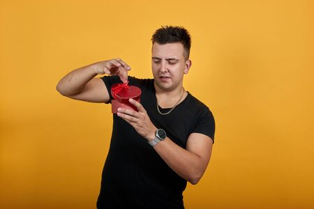 Handsome caucasian young man wearing black shirt isolated on orange background in studio keeping pink box, looking on it, takes gift out. People sincere emotions, lifestyle concept. Stok Fotoğraf - 137537415