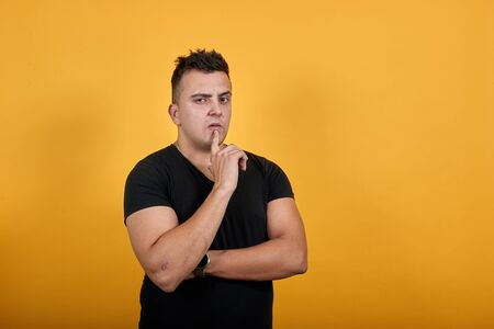 Handsome caucasian young man wearing black shirt isolated on orange background in studio keeping finger on mouth, hugging his stomach. People sincere emotions, lifestyle concept. Stok Fotoğraf