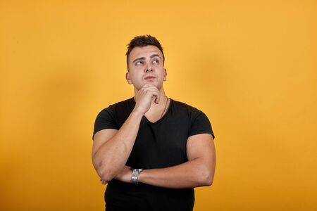 Focused young man wearing black shirt isolated on orange background in studio keeping hand on chin, thinking, holding other hand on elbow. People sincere emotions, lifestyle concept.