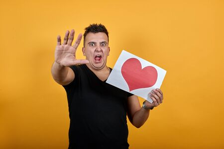 Aggressive young man wearing black shirt isolated on orange background in studio keeping picture of heart, scream, showing palm at camera People sincere emotions, lifestyle concept.