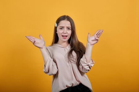 Attractive caucasian young woman looking at camera, spreads hands wearing fashion pastel shirt isolated on orange background in studio. People sincere emotions, lifestyle concept.