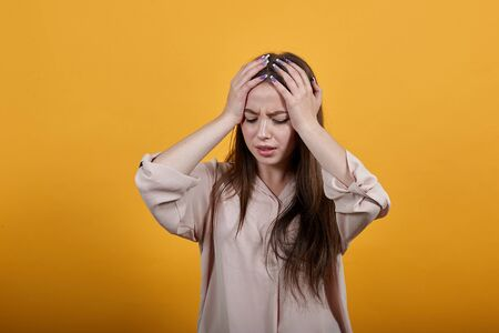 Caucasian brunette woman in fashion pastel shirt keeping hands on head, having headache isolated on orange background in studio. People sincere emotions, lifestyle concept. Stok Fotoğraf - 137537441