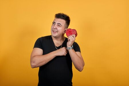 Handsome caucasian young man wearing black shirt isolated on orange background in studio waving red box, winks. People sincere emotions, lifestyle concept. Stok Fotoğraf - 137537443