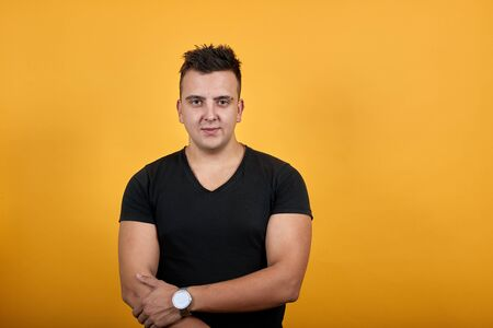 Handsome caucasian young man wearing black shirt isolated on orange background in studio looking at camera, keeping hands crossed. People sincere emotions, lifestyle concept. Stok Fotoğraf