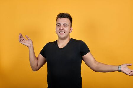 Charming young man wearing black shirt isolated on orange background in studio spreads hands, confused. People sincere emotions, lifestyle concept. Stok Fotoğraf