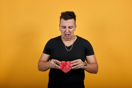 Disappointed young man wearing black shirt isolated on orange background in studio keeping box in hand, squeezing face. People sincere emotions, lifestyle concept.