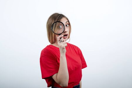 Serious caucasian woman keeping magnifier glass, looking on it wearing fashion red shirt isolated on white background in studio. People sincere emotions, lifestyle concept. Stok Fotoğraf