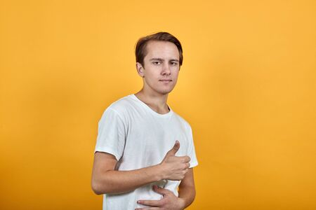 Man in a white t-short cropped look confident look. He gives thumbs up sign that everything is fine
