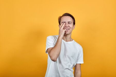 Cheerful nice guy in a white T-shirt on a yellow isolated background. Covers his eye with a few fingers