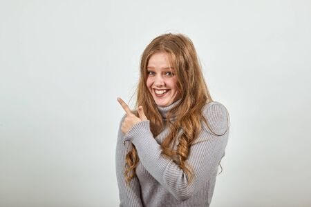 a young beautiful red-haired woman in a gray sweater smiles and points her index finger in the direction, happy and satisfied