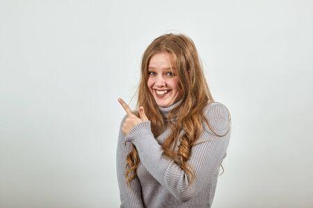 een jonge mooie roodharige vrouw in een grijze trui lacht en wijst haar wijsvinger in de richting, blij en tevreden