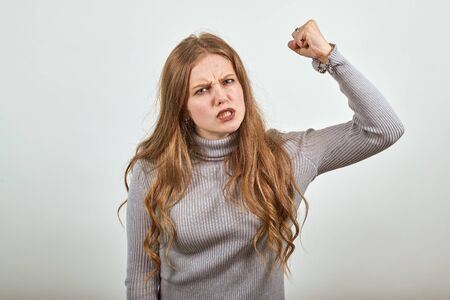 A young beautiful red haired woman in gray sweater an irritated angry lady shakes her fist in anger