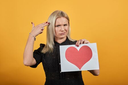 Young blonde girl in black dress on yellow background an evil woman holds piece of paper with red heart in hand and puts finger to temple, simulating suicide