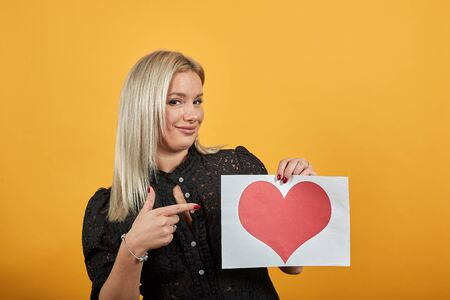 Young blonde girl in black dress on yellow background a happy woman holds piece of paper with red heart in hand, points finger at it Фото со стока