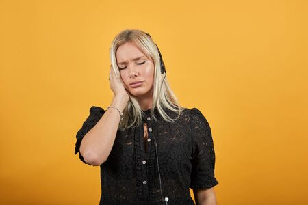 Young blonde girl in black dress on yellow background upset woman listens to music on headphones with an unhappy expression on her face
