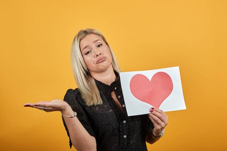 Young blonde girl in black dress on yellow background upset a woman holds piece of paper with red heart in hand, makes gesture of helplessness Фото со стока