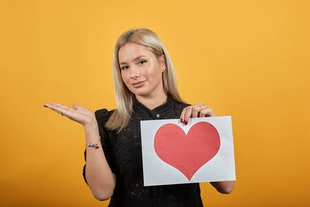 Young blonde girl in black dress on yellow background happy woman holding a piece of paper with a red heart and a hand gesture