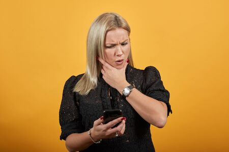 Young blonde girl in black dress on yellow background a disgruntled woman looks and is annoyed at the phone
