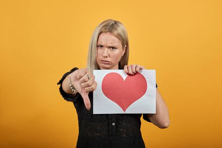 Young blonde girl in black dress on yellow background an irritated woman holds piece of paper with red heart in hand turns thumb down Фото со стока