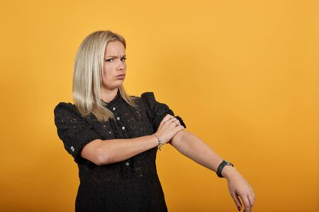 Young blonde girl in black dress on yellow background determined woman rolls up her sleeves