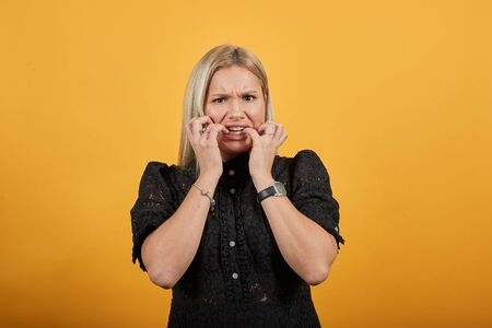 Young blonde girl in black dress on yellow background annoyed woman put her fingers in mouth Фото со стока