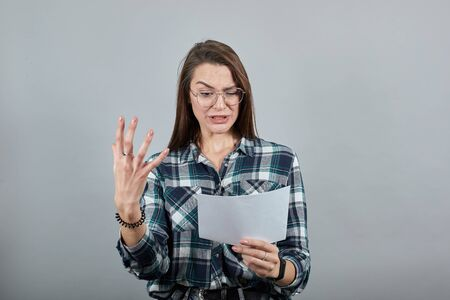 Young brunette girl blue green in checked shirt on grey background an irritated woman with glasses holds piece of paper in hand , an angry expression on face
