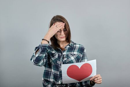 Young brunette girl blue green in checked shirt on grey background, unhappy woman with glasses holds piece of paper with red heart in hand Фото со стока