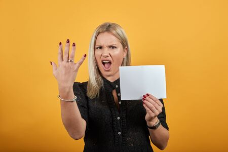 Young blonde girl in black dress on yellow background an irritated woman holds an empty sheet of paper in hand and demosnstrut fingers Фото со стока