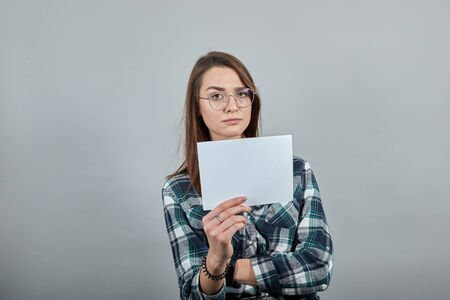 Young brunette girl blue green in checked shirt on grey background insulted woman with glasses shows a white sheet of paper