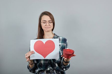 Young brunette girl blue green in checked shirt on grey background an offended woman in glasses holds a gift, piece of paper with red heart Imagens